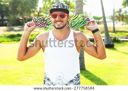 Handsome Man in sunglasses and cap,Travel concept with city on background.Sunshine portrait of young hipster with board and travel bag,opposite palms.Swag man,hipster man in swag outfit,cool beard  - stock photo