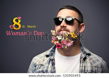 Handsome man in sunglasses with flowers in beard on dark background. Text 8TH MARCH, WOMAN'S DAY