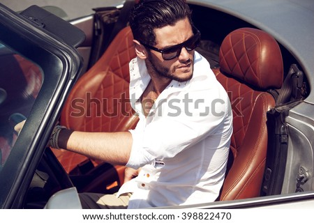 Handsome man in the car. Luxury life.