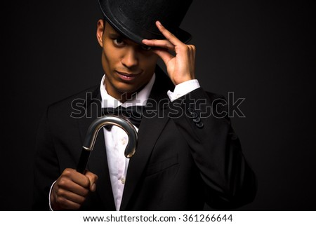 Handsome man in top hat posing with cane - stock photo