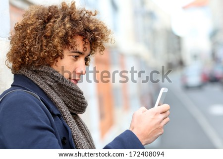 Handsome man in town using smartphone - stock photo