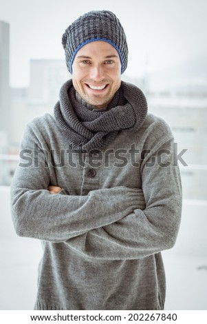 Handsome man in warm clothing smiling at camera on a chilly day - stock photo