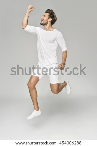 Handsome man in white clothes jumping in euphoria