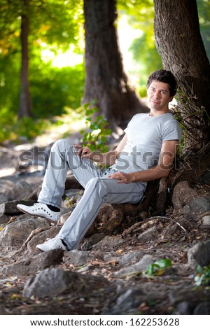 Handsome man in white clothes lying under tree in park