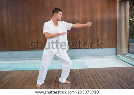 Handsome man in white doing tai chi in health spa - stock photo