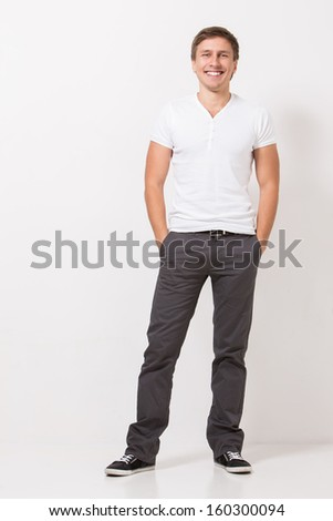 Handsome man in white t-shirt and grey trousers is posing over a white background - stock photo
