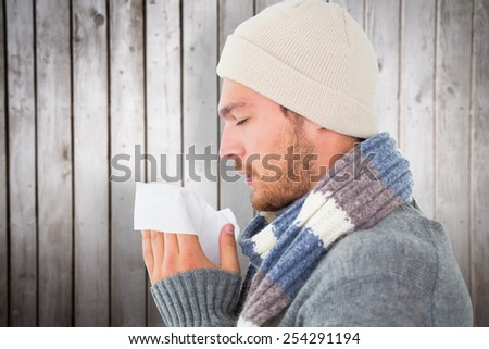 Handsome man in winter fashion blowing his nose against wooden planks - stock photo