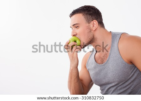 Handsome man is eating a green apple with pleasure. He likes healthy food. Isolated on background and copy space in left side - stock photo