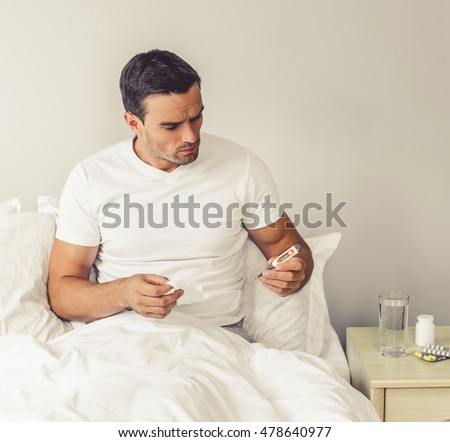 Handsome man is having a common cold. He is holding a thermometer and paper tissue while sitting in bed at home