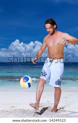 Handsome man is playing on the beach - stock photo