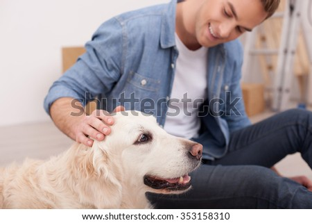Handsome man is playing with his dog. He is sitting and smiling. The man is stroking the pet with joy