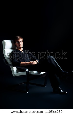 Handsome man is sitting in the armchair over black background. - stock photo