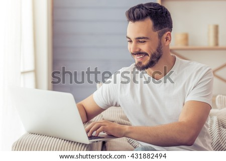 Handsome man is using a laptop and smiling while sitting on the sofa at home - stock photo