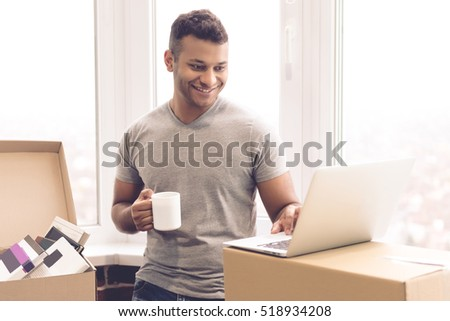 Handsome man is using a laptop, holding a cup and smiling while standing near the packed boxes ready to move