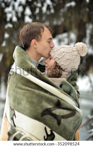 Handsome man kiss on the forehead her beloved,beautiful,pretty,attractive girl with sweater,mittens,winter,cold,snow forest,hut,love,happy,togetherness,couple,lucky,together,two,young,family,romance - stock photo