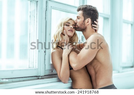 Handsome man kissing blond beauty - stock photo