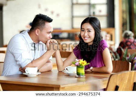handsome man kissing his girlfriend hands during dating at coffee shop - stock photo