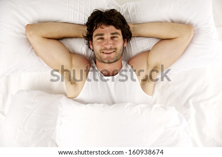 Handsome man laid smiling enjoying a lie-in in the morning in a white bed - stock photo