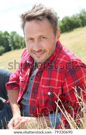 Handsome man laying down meadow - stock photo