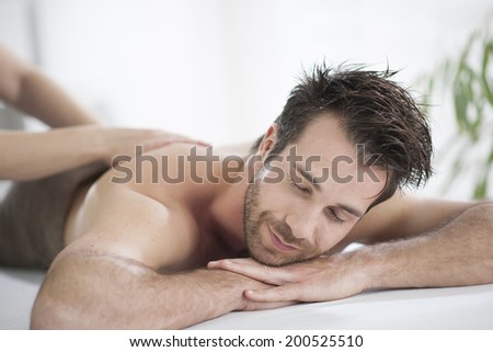 Handsome man laying on a massage bed - stock photo
