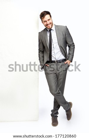 handsome man leans on panel - stock photo