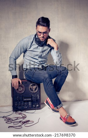 handsome man listening to music on a magnetophone against grunge wall - stock photo