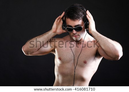 handsome man listening to music on headphone black background - stock photo