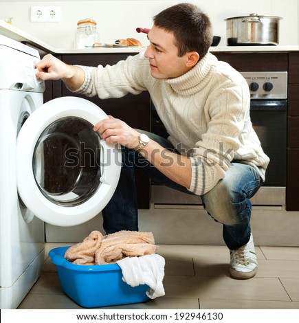 Handsome man loading the washing machine in kitchen