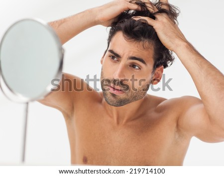 Handsome man looking at himself in the bathroom mirror. Checking for gray hair. - stock photo