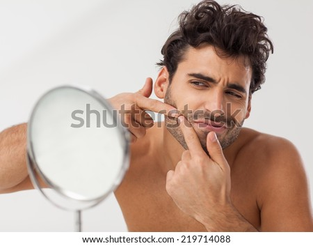 Handsome man looking at himself in the bathroom mirror. Squeezing pimple. - stock photo