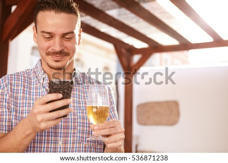 Handsome man looking at his cellphone with a secretive smile while holding a glass of beer in the other hand