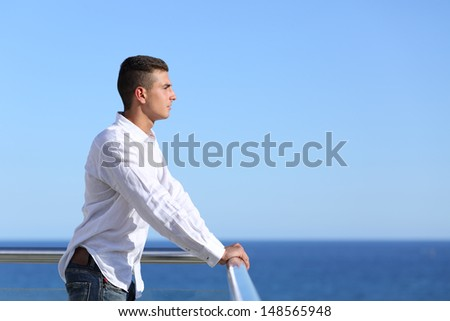 Handsome man looking at the horizon with the sea and a blue sky in the background               - stock photo