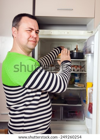 Handsome man looking for something in refrigerator  at kitchen - stock photo