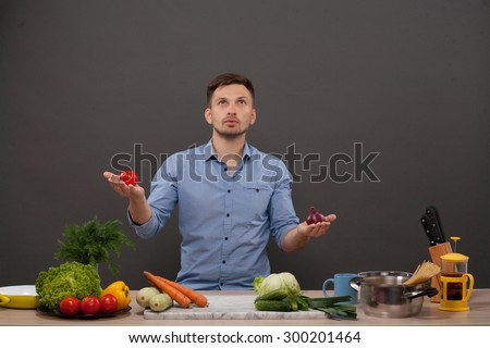 Handsome man looking upwards with a pensive thoughtful look while standing in his kitchen. Chef is going to cook and prepare a meal from a variety of fresh vegetables. - stock photo