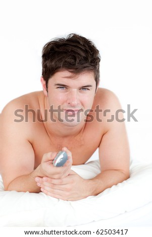 Handsome man lying on his bed and holding a remote against a white background - stock photo