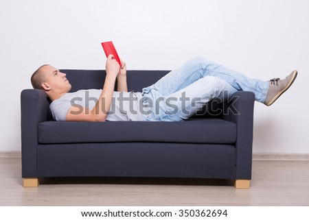 handsome man lying on sofa and reading book at home - stock photo