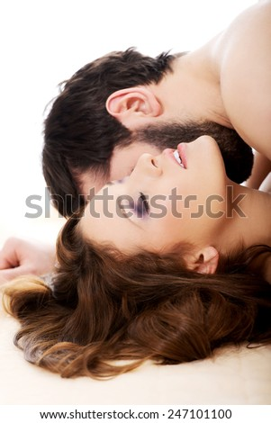 Handsome man lying on woman in bed and kissing her.