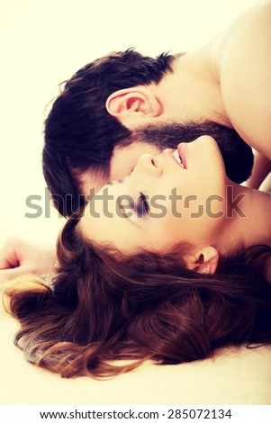 Handsome man lying on woman in bed and kissing her. - stock photo