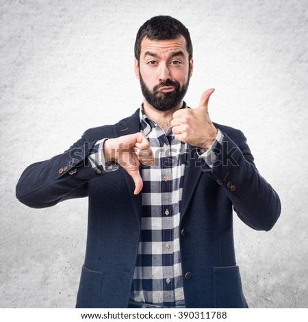 Handsome man making good-bad sign - stock photo