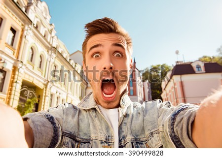 Handsome man making selfie and grimacing with opened mouth - stock photo
