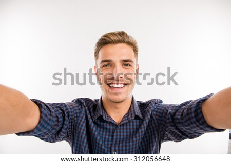 Handsome man making selfie and smiling - stock photo