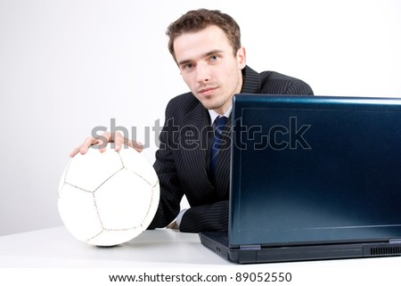 Handsome man, male model as charming businessman in suit with ball dreaming thinking about football soccer near computer in office - stock photo