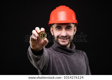 Handsome man miner in protective hemlet pointed bitcoin isolated on black