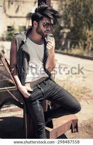 handsome man model dressed punk, hipster posing dramatic in grunge location - stock photo