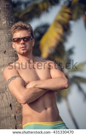 Handsome man model posing on the sea rock near beach. man beach, man ocean, man model sea, man travel, guy model chest, man model beach posing, man model sexy, man sand, handsome man, Muscle man - stock photo