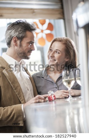 handsome man offering a gift to his girlfriend in a bar - stock photo