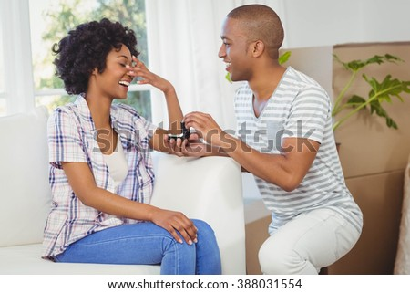 handsome man offering engagement ring to his girlfriend in the living room