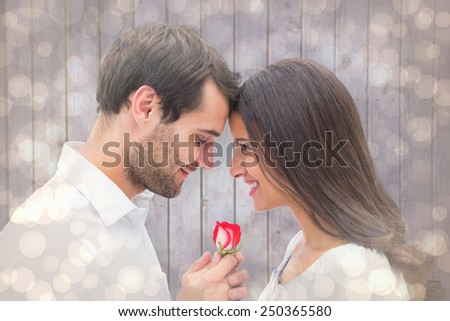 Handsome man offering his girlfriend a rose against light glowing dots design pattern - stock photo