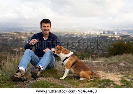Handsome Man on a Hill Top with his Dog and a treat City in the background - stock photo