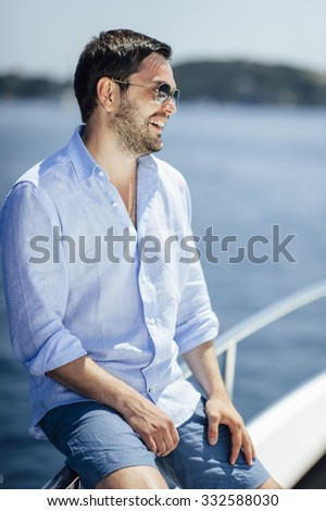 Handsome man on a yacht enjoy bright sun light on vacation